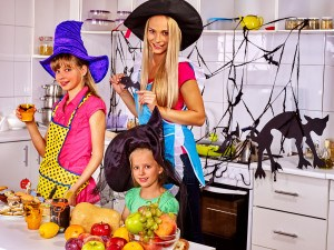 Happy family with children preparing halloween food. Children with mother preparing festive dinner on halloween holiday.