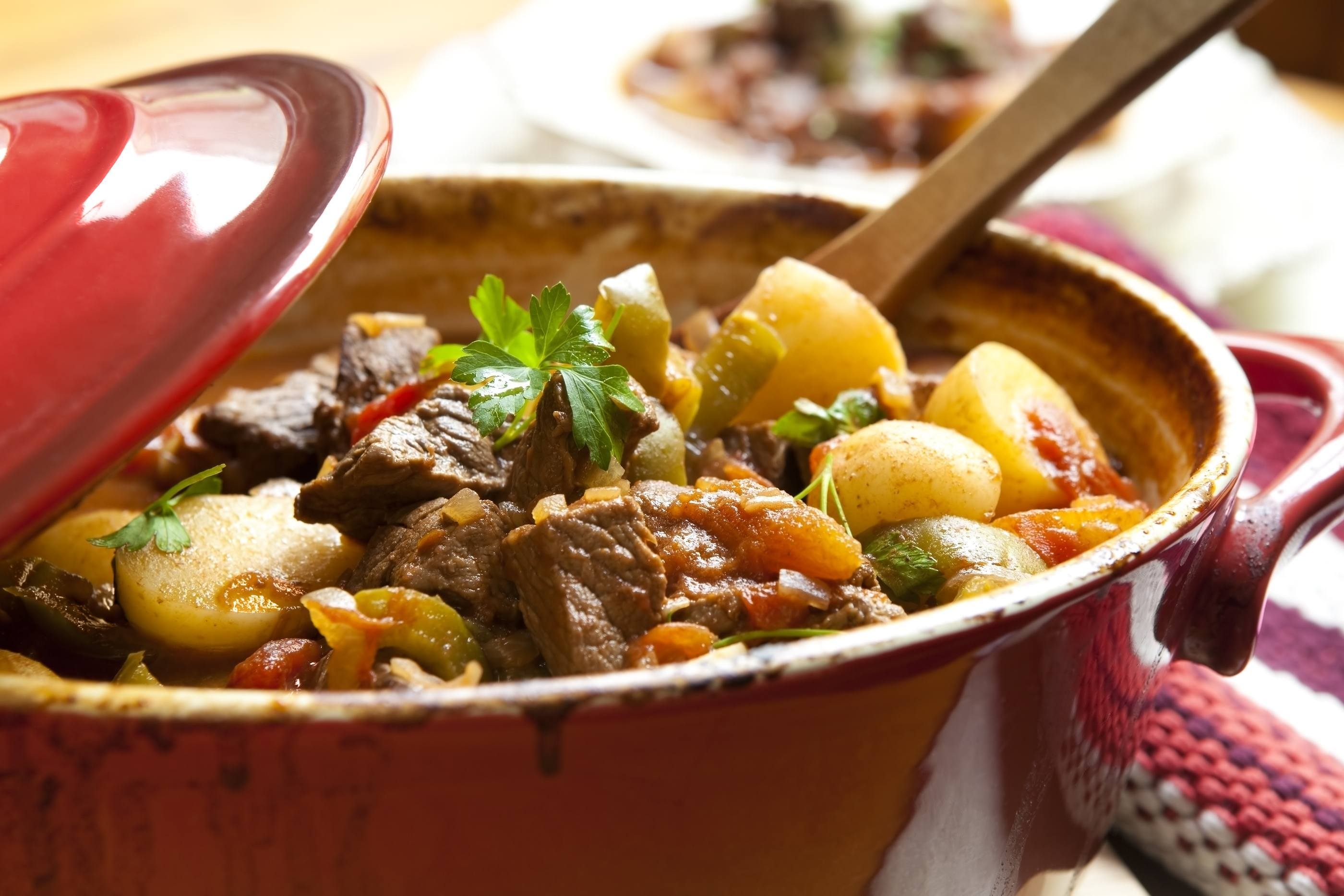 Traditional goulash or beef stew in red crock pot ready to serve. Shallow DOF.