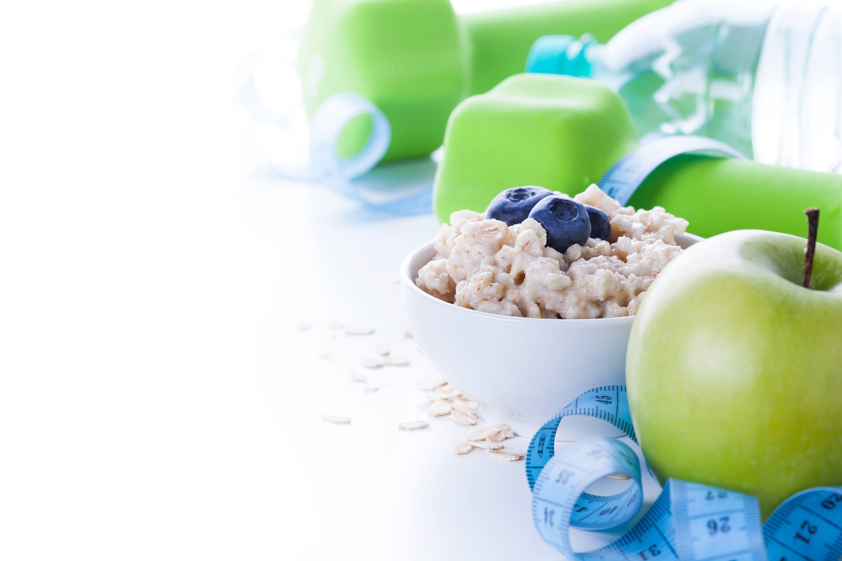 Fitness frame with energy breakfast oatmeal apple and mineral water with sport tools on background. Healthy weight loss concept with copy space.