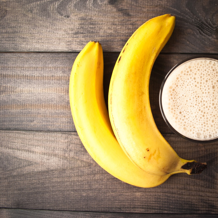 Glass of banana smoothie and fresh bananas on brown wooden background. Top view