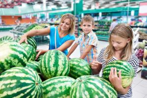 Selecting Melons at Grocery Store