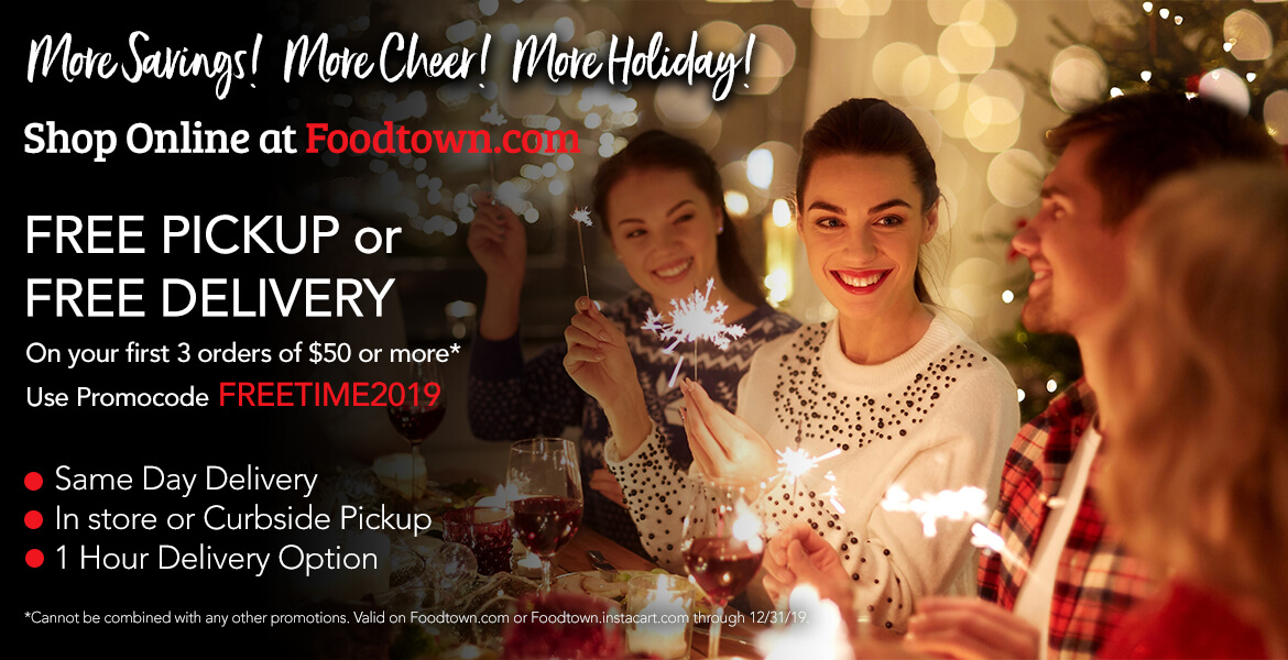 Group of friends celebrating the holidays with food and drink, holding sparklers. Advertising free pickup or delivery of groceries.