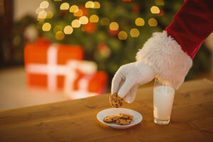 Santa Claus reaching for a plate of cookies and milk that were left out for him.