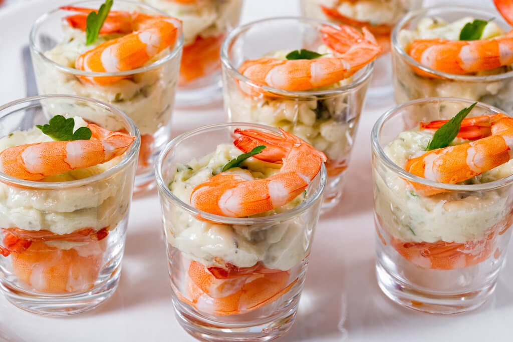Individual shrimp cocktail shooters in a glass cup with homemade aioli sauce