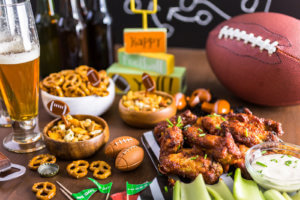 buffalo wings with assorted football game snacks on a table