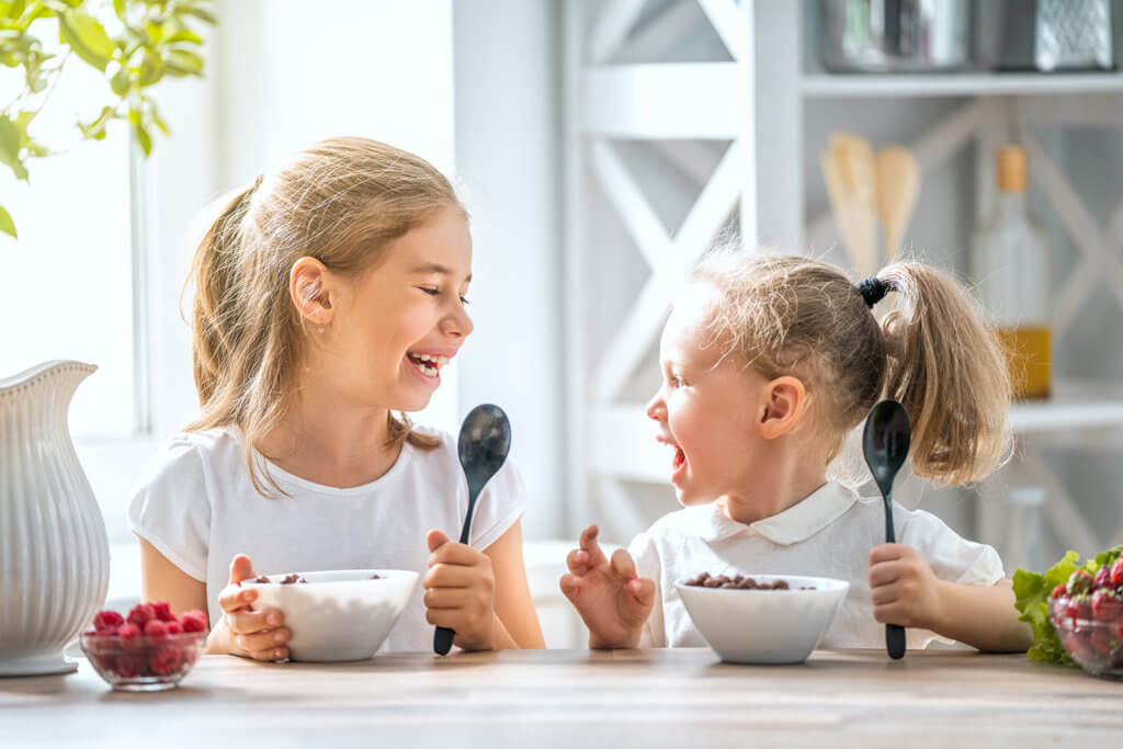 Two young girls sitting at the table eating breakfast