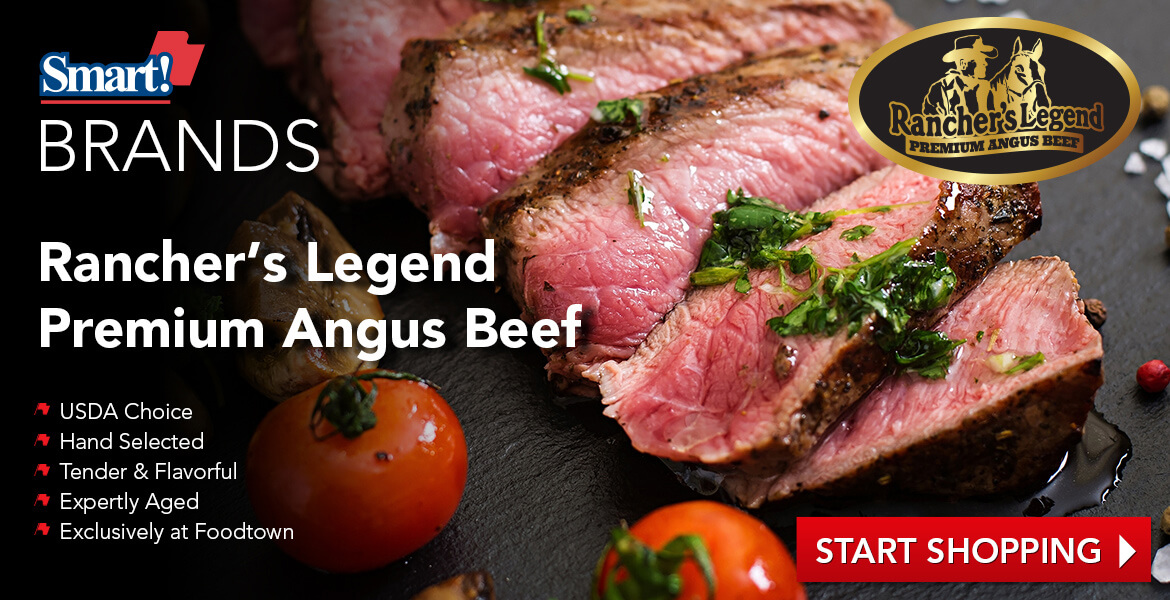 a cut juicy steak on a black slate cutting board with tomatoes and mushrooms on the side