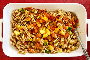 whole grain pasta cooked in a baking dish with vegetable sauce