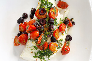 a baked tomato olive cod fish on a plate
