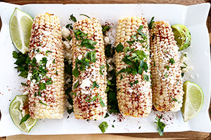 Mexican street corn on a plate with sliced limes on the side