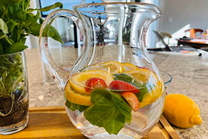 strawberry, basil and lemon infused water in a pitcher on the table