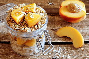 a jar of breakfast oats with fresh peaches